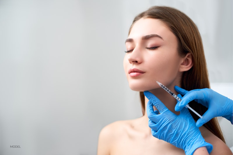 Young women getting a dermal filler injection with her cosmetic surgeon.