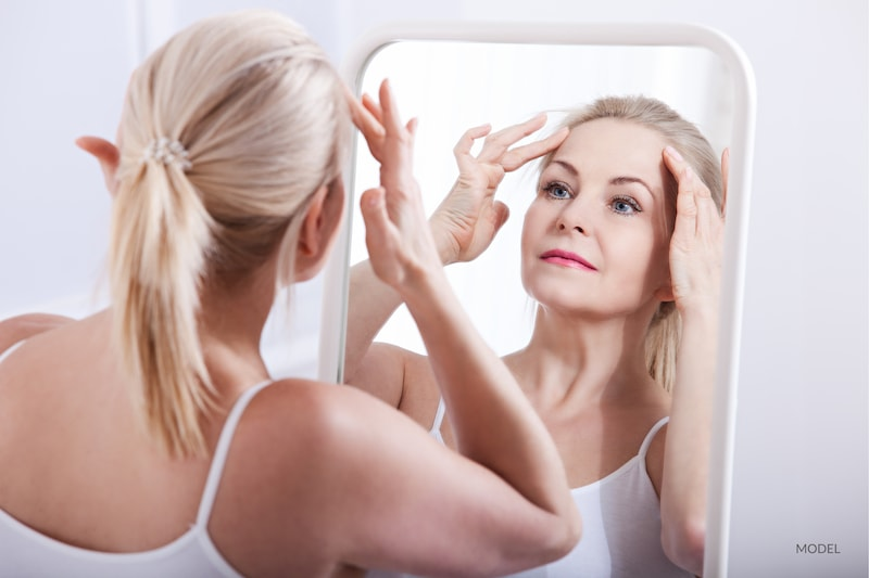 Middle-aged blond woman examining her forehead in the mirror.