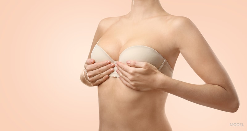 Woman's hands covering her breasts over her bra on a peach background.